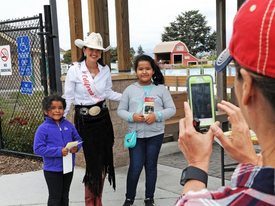 Belen Tienda, 6, and her sister Angela, 11, pose for photos at Tatum's Garden with Miss California Rodeo Salinas Taylor Howell.