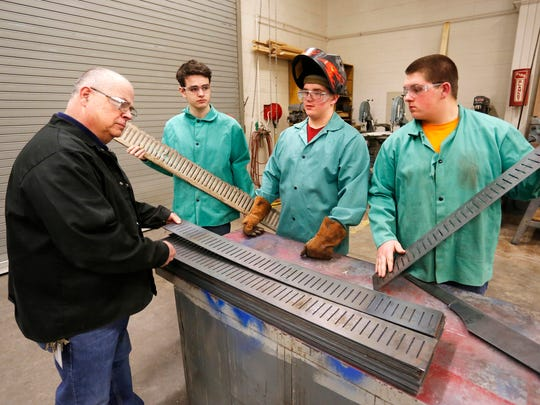 Rob Jakes, from left, is joined by Reid Gamble and twins Jacob and Joshua Rainey as they examine drain covers Monday, March 12, 2018, at McCutcheon High School. Students in Jakes' Ag Power Structure and Technology class made the steel drain covers using a CNC plasma cutter. The drain covers will replace drain covers that were rusted and worn in the kennels of the Humane Society of Clinton County. Jakes said the original drain covers lasted 13 years. He hopes the drain covers manufactured by his students will last 20-25 years.