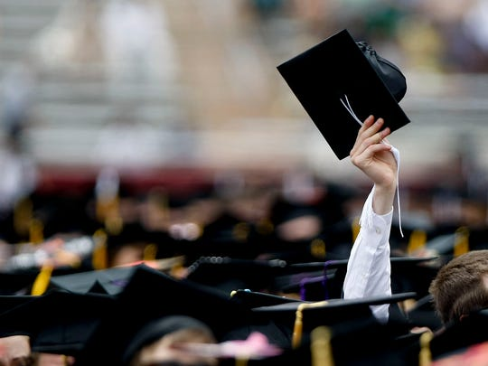 A graduating student holds his cap in the air during.