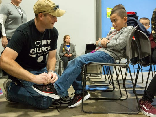 Mesilla Park Community Church member Tristan Gilbert helps Jaden Medina, 7, try on a brand new sneakers on Saturday, March 17, 2018 during Soles 4 Souls Distribution Day at Mesilla Park Community Church.
