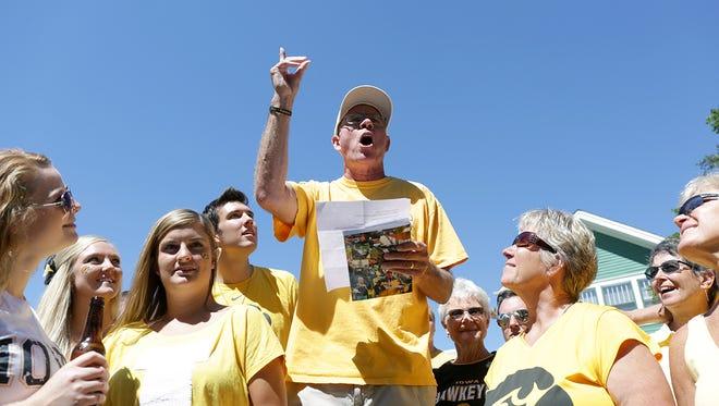 "Carl ""Sandburg"" Schwendinger, the ""Hawkeye Poet,"" reads a poem before the Hawkeyes' home football game against Ball State on Saturday, Sept. 6, 2014, at Kinnick Stadium in Iowa City, Iowa."