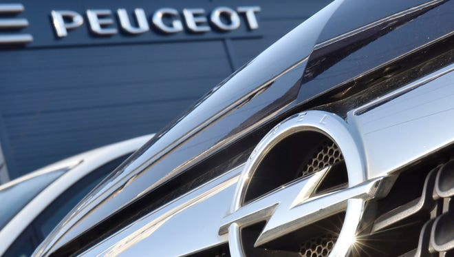 An Opel car, in front, is offered for sale by a Peugeot dealer in Gelsenkirchen, Germany, Tuesday, Feb. 14, 2017.