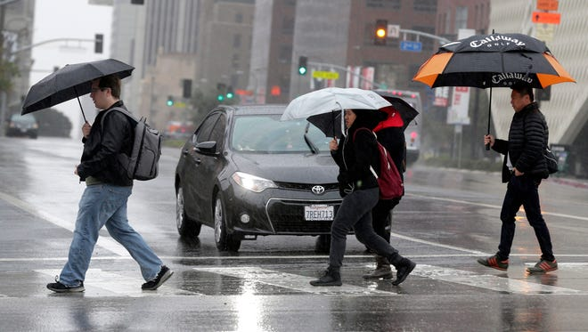 Pedestrians cross a rainy street in downtown Los Angeles on Monday, Feb. 6, 2017. Another storm is forecast to slam into southern California on Friday.