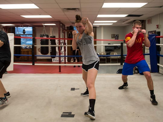 Indiana State Trooper Kaitlyn Greene, from left, Kentucky State Inspector Taylor Griffith and Indiana State Trooper Jordan Lee work on foot work and jabs during a Guns team practice at the Guns and Hoses Gym in Old Vanderburgh County Courthouse on Thursday, March 27, 2018. The Guns and Hoses event pits law enforcement officers against firefighters in night of charity boxing matches on April 7.