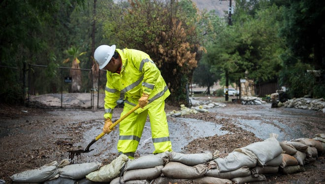 Paul Nieto, of LA County Public Works, clears debris along Grand Avenue below the Colby Fire burn area on Tuesday, Dec. 2, 2014. Heavy rain from a powerful Pacific storm swept through California on Tuesday, providing some relief from a three-year drought. (AP Photo/San Gabriel Valley Tribune, Watchara Phomicinda)