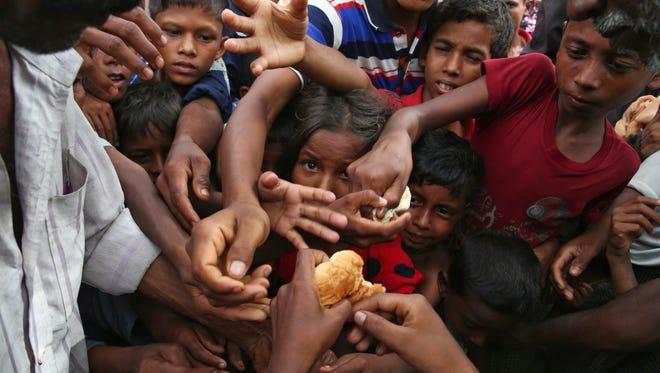Myanmar's Rohingya Muslim ethnic minority children stretch their hands out to receive food distributed by locals at the Kutupalong makeshift refugee camp in Cox's Bazar, Bangladesh, Wednesday, Aug. 30, 2017.
