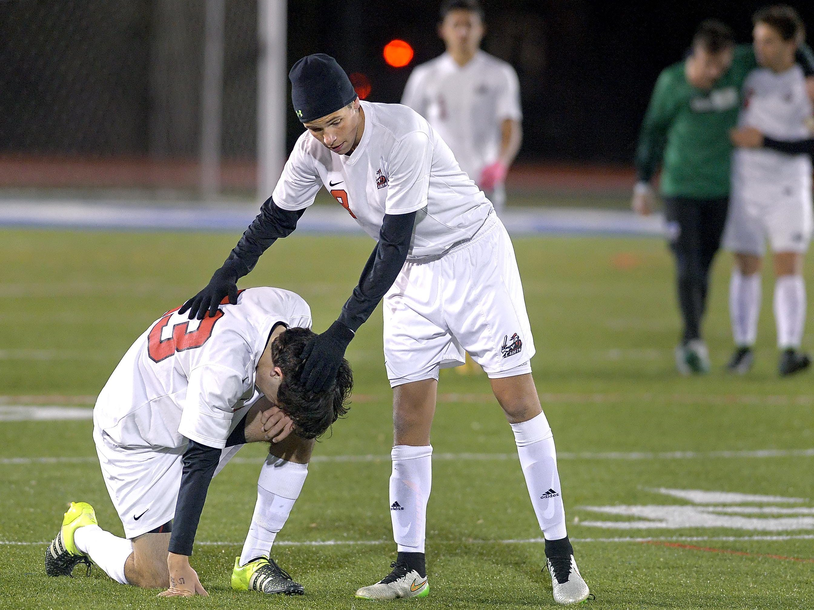 Hilton's Brady Farrell, center, consoles Tyler Nettnin following their loss in the NYSPHSAA Boys Soccer Championships Class AA semifinal played at Middletown High School on Saturday, November 14, 2015. Hilton's season ended with a 7-3 loss to Walt Whitman-XI.