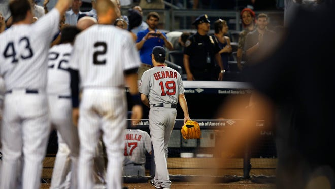 Boston Red Sox relief pitcher Koji Uehara (19) leaves the field as the Yankees, including relief pitcher Adam Warren (43) and Derek Jeter (2), wait at home plate for Chase Headley, who hit a ninth-inning home run off Uehara to lift the Yankees to a 5-4 victoryThursday night at Yankee Stadium.
