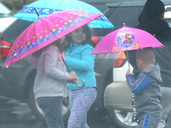 During a downpour on Saturday, kids use umbrellas to