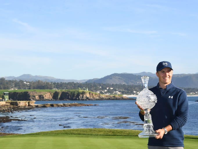 Jordan Spieth poses with the trophy on the 18th green