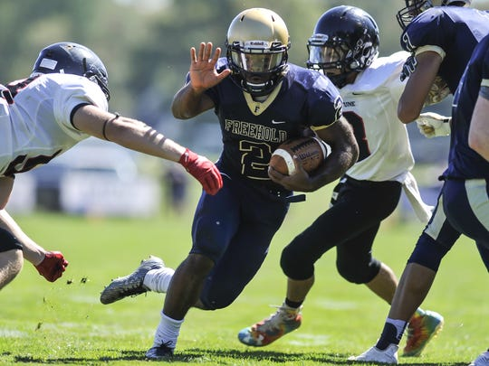 Freehold Boro quarterback Ashante Worthy looks to elude a Neptune defender during the first quarter of their game in Freehold on  Sept. 23, 2017.