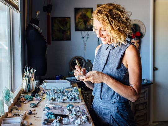 Artist Adina Mills works on some of her creations.