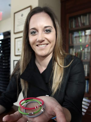 Anna Bruno poses for a photo with her bracelets at the Day House on Thursday, Feb. 6, 2014.