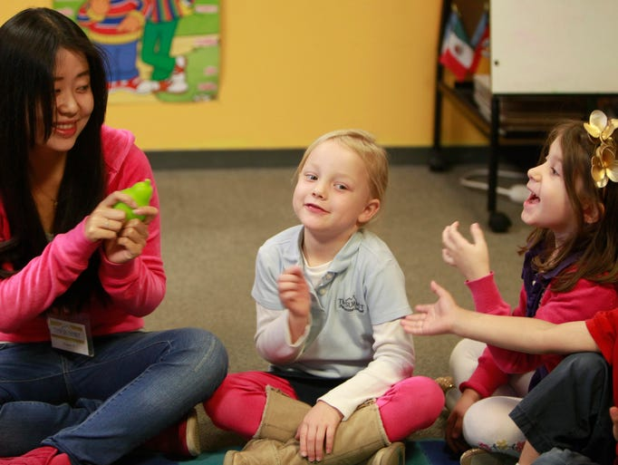 Xinyue Yu prepares to pass a toy pear around the circle as she teaches students words in Mandarin at Summit Preparatory School of Southwest Missouri on Wednesday, April 16, 2014.