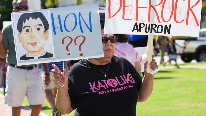 """Members and supporters of the Concerned Catholics of Guam and the Laity Forward Movement protest with signs reading: """"Defrock Apuron"""" and """"Hon - No More $$ For RMS"""" at Dulce Nombre de Cathedral Basilica in Hagatna on July 31."""