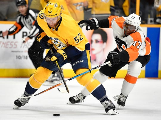 Philadelphia Flyers right wing Wayne Simmonds (17) tries to grab the puck from Nashville Predators defenseman Matt Irwin (52) during the second period of the home opener at Bridgestone Arena in Nashville on Oct. 10, 2017.