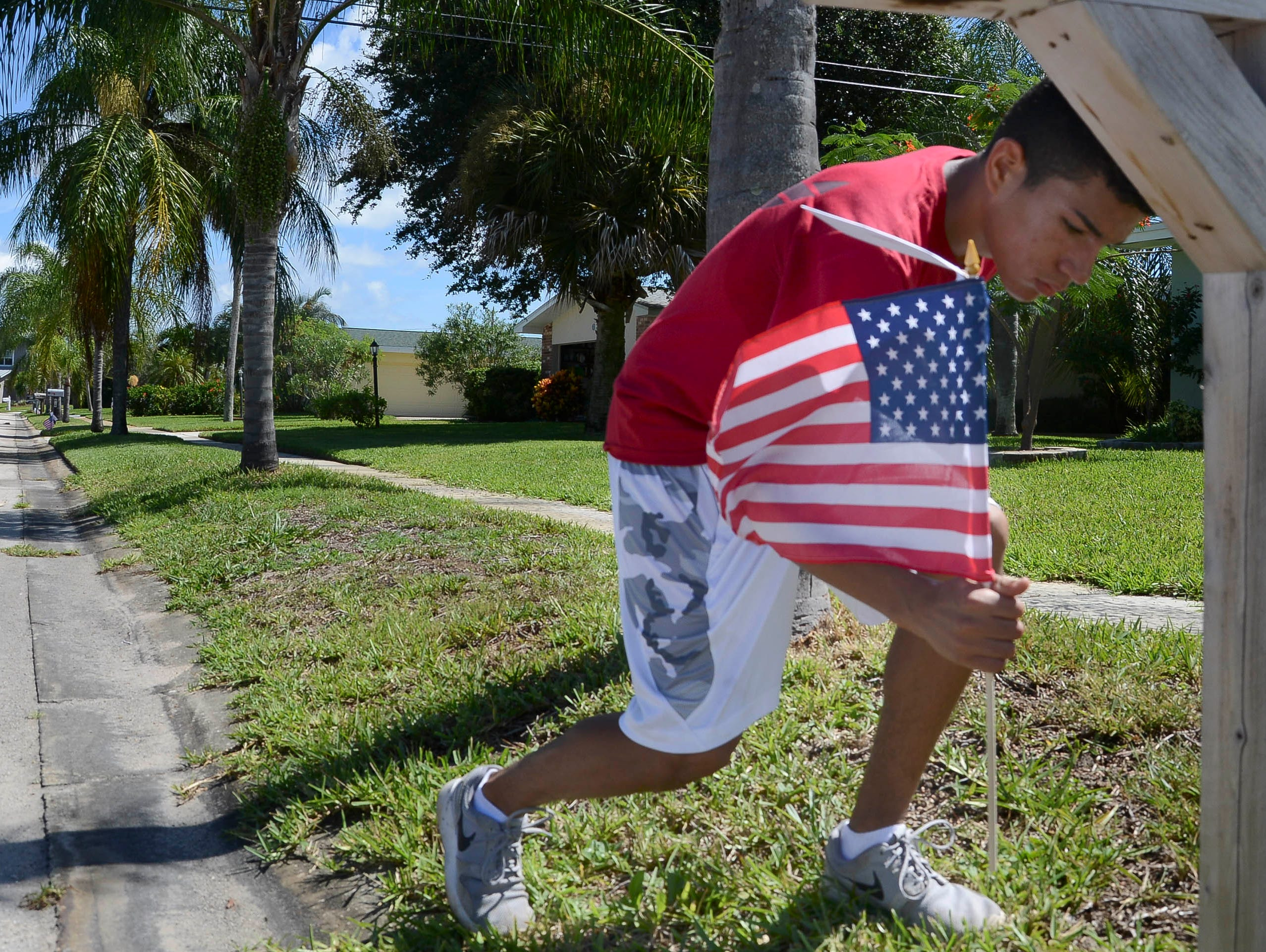 Kobe Thompson helps set out American flags Thursday morning in Satellite Beach. Students from Satellite High's football and ROTC squads help distribute American flags as part of a fundraiser for the school.
