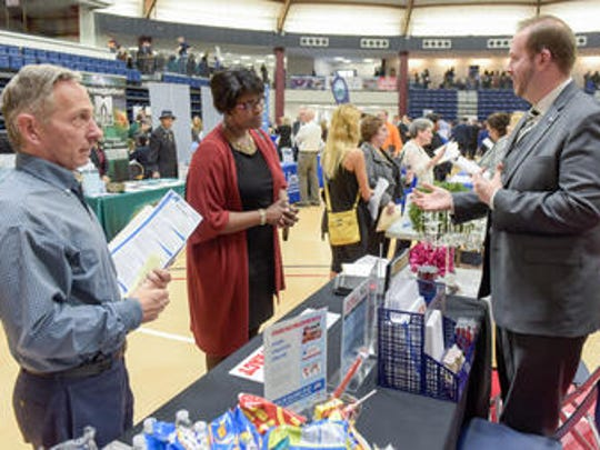Abram Covella (RIGHT) a real estate strategist representing ReMax speaks with Joe Eskenazi (left) Freehold and Annette LaBarbera, Eatontown.