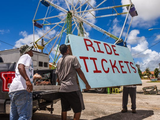 Employees of ride vendor Parté Zone, unload a sign for their ticket booth on Tuesday, July 11, 2017, as they make last-minute preparations at the Paseo de Susanna in Hagåtña. The 73rd Liberation Carnival is scheduled to open Wednesday evening, with the coronation of the Liberation queen at 6 p.m. The carnival will run 6 p.m. to 10 p.m., Wednesday through Sunday, ending Aug. 13.