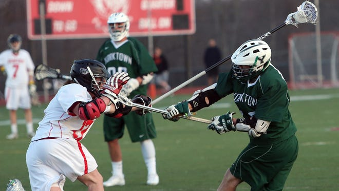 Yorktown's Connor Vercruysse, right, fires a shot by Somers' Luke Roediger  (17) for a first half goal during a boys lacrosse game at Somers High School April 10, 2014. Yorktown won the game 14-6.