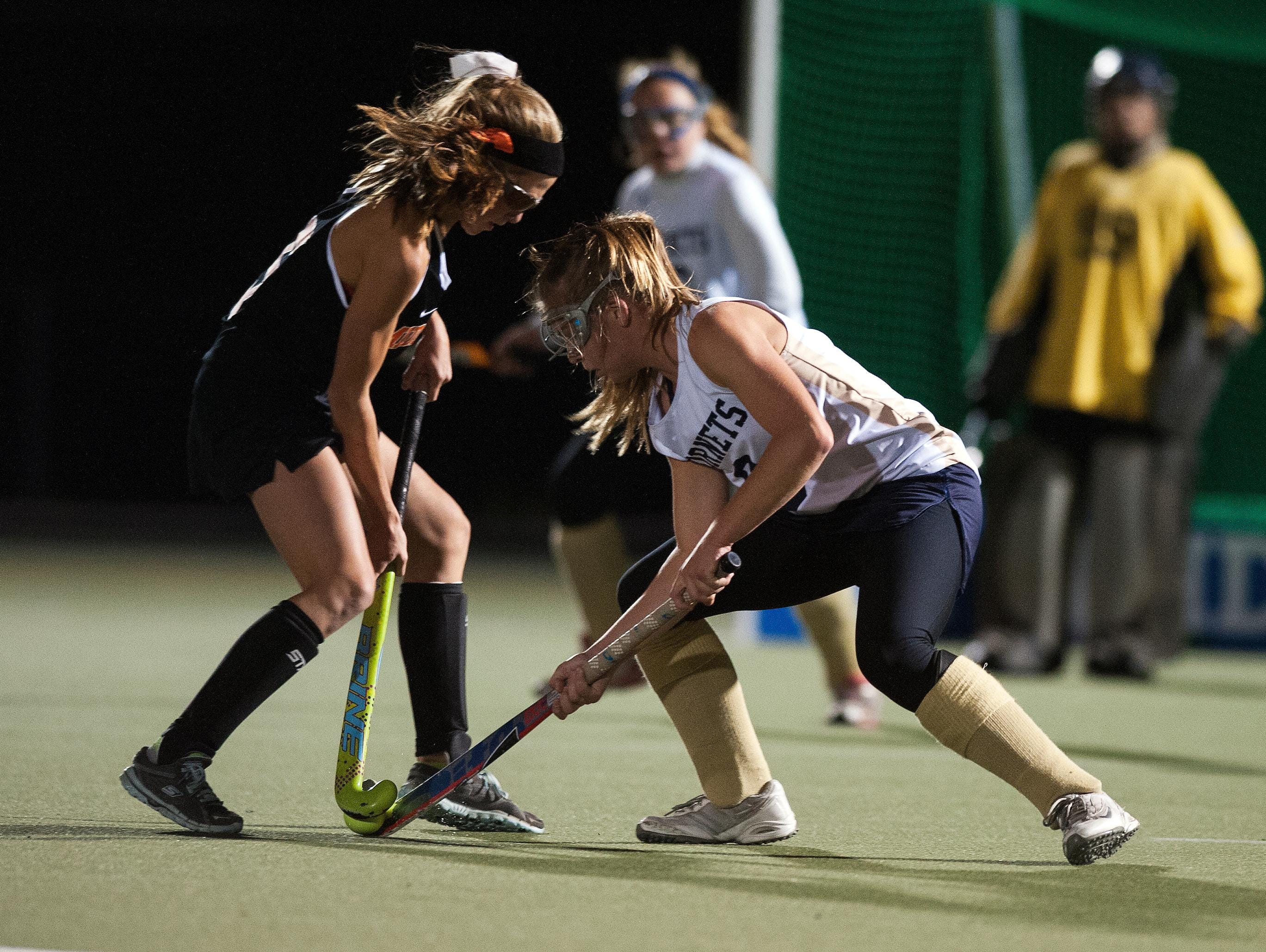 Middlebury's Lily Smith, left, battles for the ball with Essex's Kathleen Young (9) during the Division I field hockey semifinal in October.