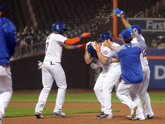 Mets right fielder Jay Bruce, center, protects himself as his teammates come out on the field to celebrate his game-winning single against the Milwaukee Brewers during the 12th inning at Citi Field on Tuesday, May 30, 2017.