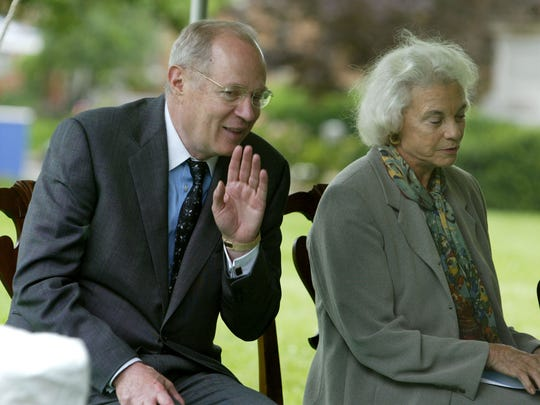 Supreme Court Justice Anthony Kennedy whispers to Justice Sandra Day O'Connor during a groundbreaking ceremony at the court in 2003.