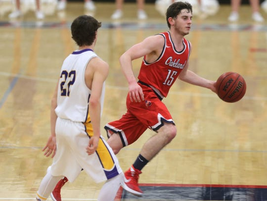 Oakland's Cooper Baughn (15) dribbles upcourt as Lawrence