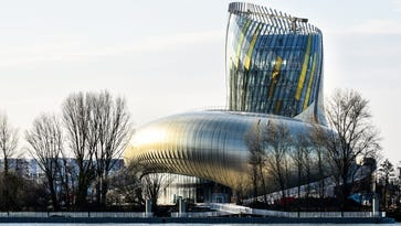 """Designed by Paris-based XTU Architects to resemble """"the swirl in a wine glass,"""" the shimmering aluminum-clad structure also recalls the currents of the river that's been the lifeblood of Bordeaux for millennia."""