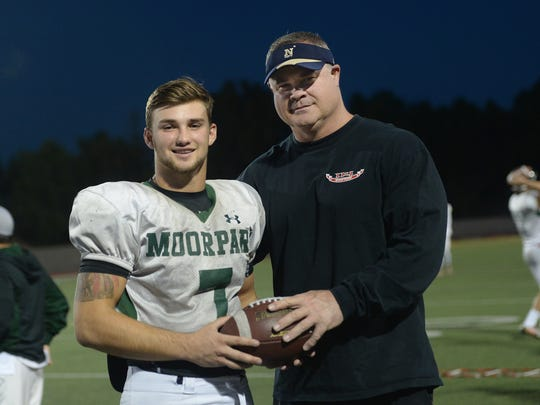 Quarterback Tyger Goslin and his father John Goslin pose for a photograph at practice last week. This year John Goslin transitioned from coach for his son to a father watching from the stands.