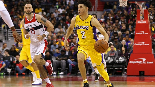 Los Angeles Lakers guard Lonzo Ball (2) dribbles the ball as Washington Wizards center Marcin Gortat (13) chases in the third quarter at Capital One Arena.