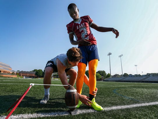 Ntirenganyi Karamba (right) receives instruction from Memphis University School kicker Trey Thomas (left) during a practice session last year. Thomas was mentoring Karamba on the ins and outs of placekicking.