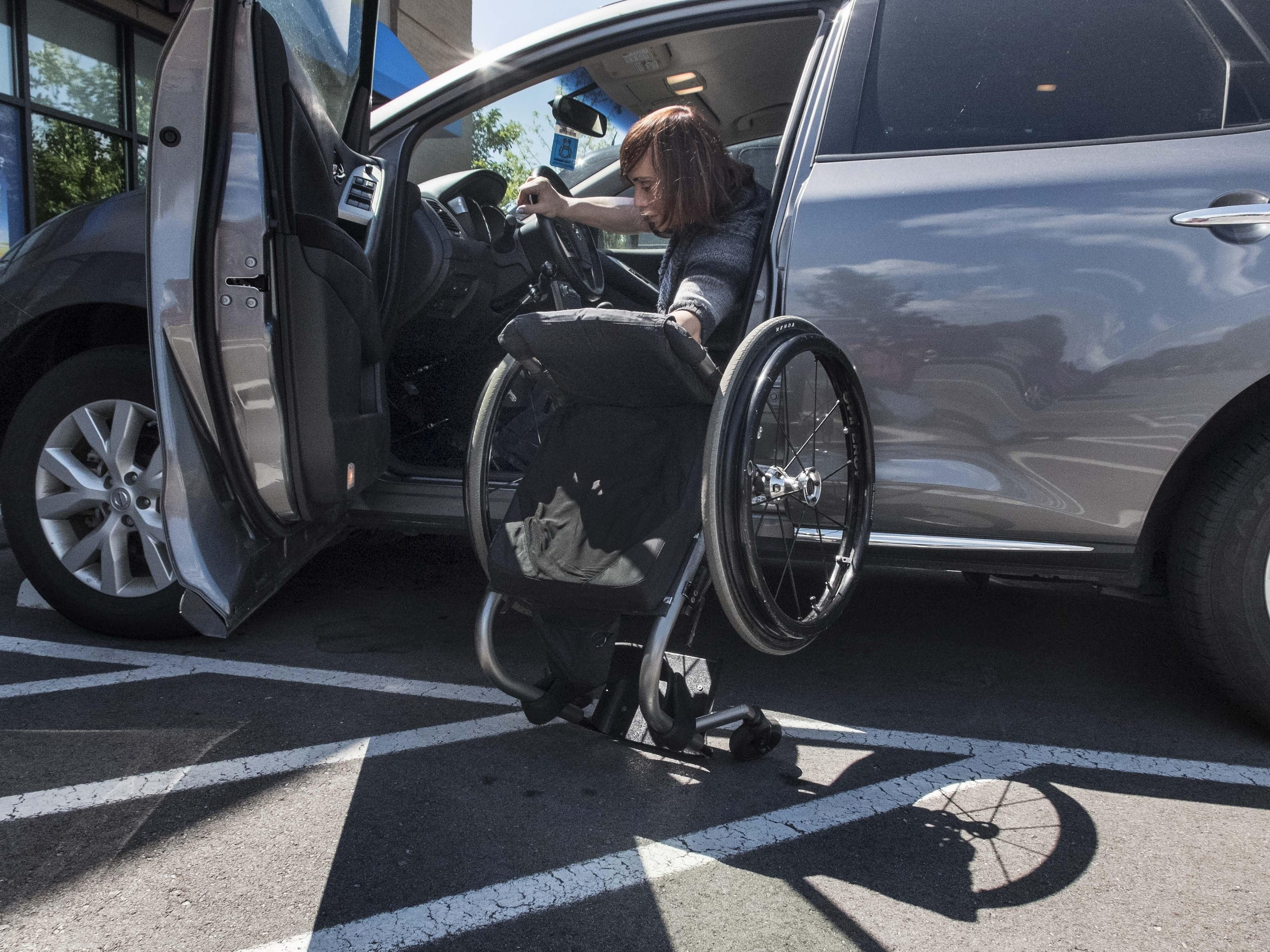 Robin Patty lifts her wheelchair into her car on Tuesday,