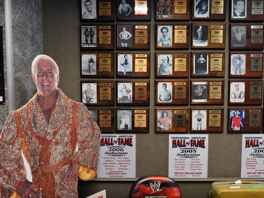 "A cardboard cutout stands next to a wall showing each class of inductees into the Professional Wrestling Hall of Fame. The hall of fame and museum first opened in New York in 1999 and includes about 140 inductees. The non-profit moved to Wichita Falls in 2016 and will celebrate its one-year anniversary in the First Wichita Building (""Big Blue"")."