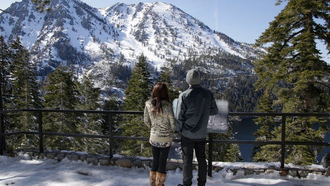In April, visitors view Lake Tahoe's snow-covered Sierra Nevada Mountains, where record snowfall made the winter the wettest since records were kept nearly a century ago in Lake Tahoe, Calif.