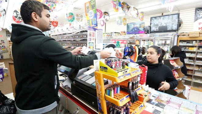 Mehul Patel, left, sells powerball tickets to Talysha Fernandez of Haverstraw at Ivy Stationers in Mount Ivy on Friday.