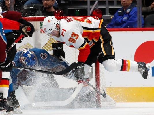 Colorado Avalanche goaltender Semyon Varlamov, left, stops a shot by Calgary Flames center Sam Bennett during the first period of an NHL hockey game Wednesday, Feb. 28, 2018, in Denver. (AP Photo/David Zalubowski)