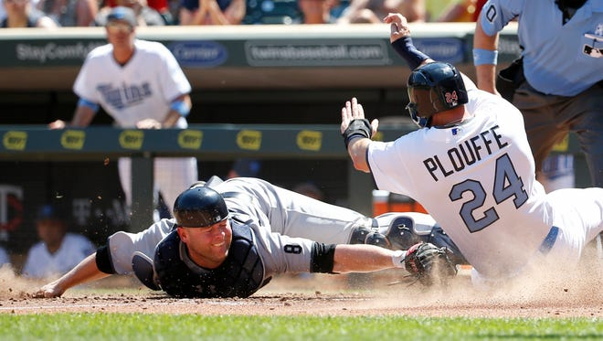 Minnesota Twins' Trevor Plouffe (24) is safe at home plate as he avoids the tag of New York Yankees catcher Brian McCann on a two-run triple by Twins' Eduardo Escobar during the sixth inning of a baseball game in Minneapolis, Sunday, June 19, 2016.
