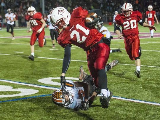 Rutland's Cam Slade, right, runs over Middlebury's Ali Abdul-Sater in the D1 state football championship in Rutland on Saturday, November 7, 2015.
