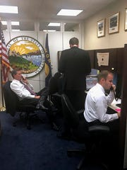 This photo provided by the office of Sen. Steve Daines, R-Mont., taken, Jan. 31, 2017, shows Sen. Daines, left, helping with a surge in constituent telephone calls to his office on Capitol Hill in Washington.  A lot of politics is about the basics, and in Congress that means answering the phone. By that measure, life on Capitol Hill in the Trump era is a struggle. Whether constituents are calling to request congressional flags, get help with a local issue — or, more likely, to register their support or displeasure with the latest move by President Donald Trump, these days they are more likely to get a busy signal or voice mail than a live human.