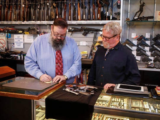 The Pawn Shop manager Matt DePhilliops, left, and owner Jeff Pocock set out an assortment of handguns to be photographed on Friday, Jan. 26, 2018, in Des Moines.