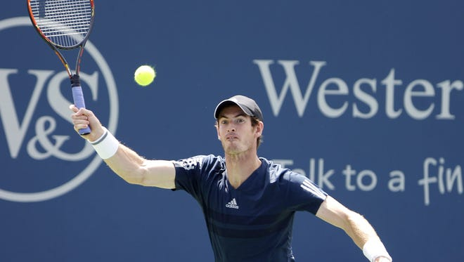 Andy Murray of Great Britain makes a hit to John Isner of the U.S. on the Grandstand during the Western and Southern Open at the Lindner Family Tennis Center in Mason. Photo shot Thursday August 14, 2014.