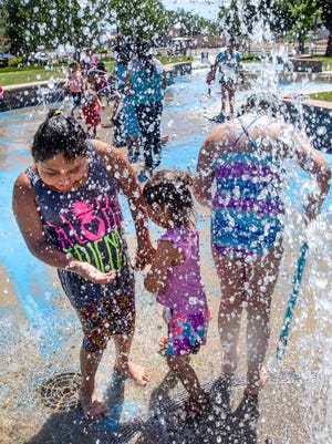 At left, Kassidy Antonio plays with her niece Eliza Rodriguez, center, along with Serenity Williams on Monday at Berg Park's Splash Pad in Farmington.