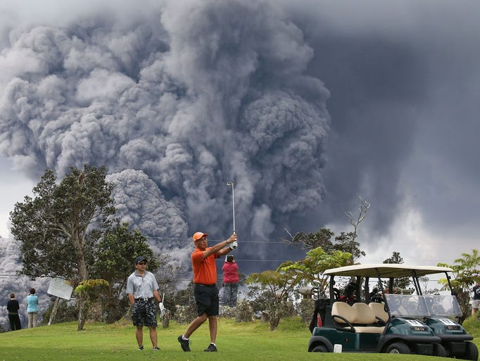 People play golf as an ash plume rises in the distance