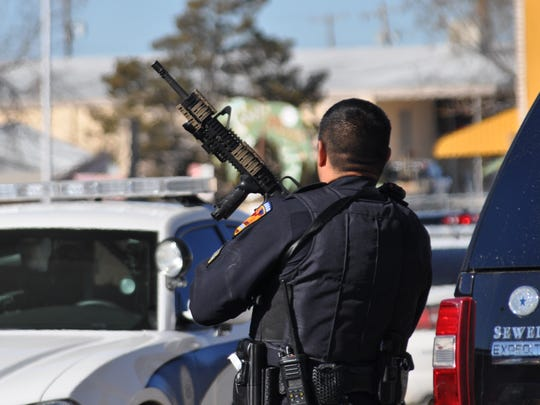 An officer with the Carlsbad Police Department assists during the execution of arrest warrants Feb. 24 near Mermod Street in Carlsbad, N.M.