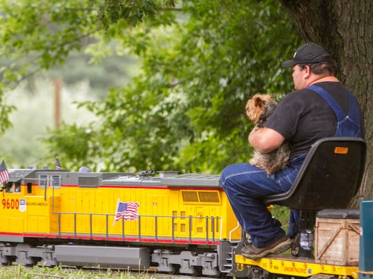 Dan Kalis holds 4-year-old Yorkshire terrier Lulu on his 7.5 gauge train as he drives it around the yard at his Howell Township residence Wednesday, June 27, 2018.