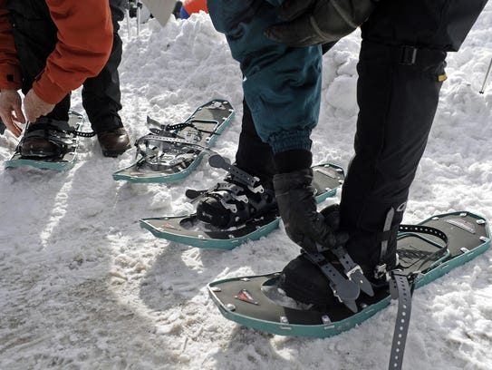 Beginning snowshoers put on their snowshoes prior to