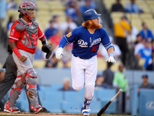 Los Angeles Dodgers' Justin Turner watches his two-run home run, next to Los Angeles Angels catcher Martin Maldonado during the first inning of an exhibition baseball game, Saturday, April 1, 2017, in Los Angeles. (AP Photo/Mark J. Terrill)