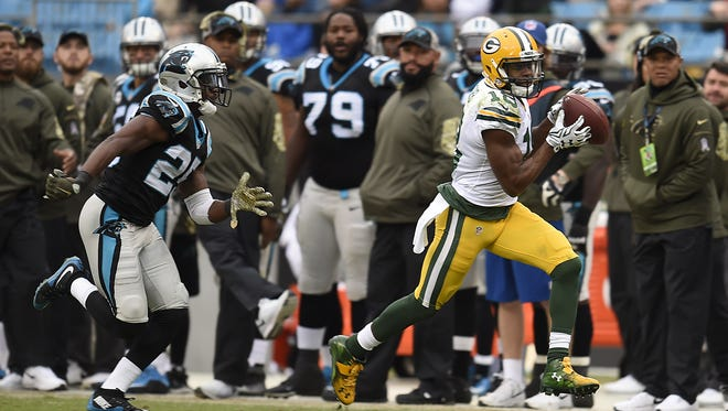 Green Bay Packers receiver Randall Cobb (18) runs away from Carolina Panthers cornerback Bene Benwikere (25) after Cobb make a catch in the third quarter during Sunday's game at Bank of America Stadium in Charlotte, NC. Cobb scored a touchdown on the play.