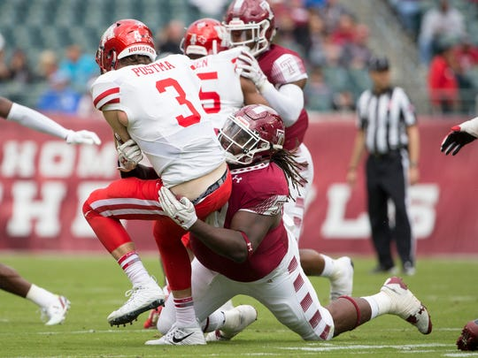 Freddie Booth-Lloyd (99) of the Temple Owls tackles